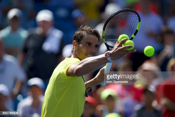 Rafael Nadal of Spain hits autographed balls in to the crowd after winning his match during a match in the Western Southern Open at the Lindner...