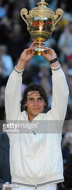 Rafael Nadal of Spain holds aloft the trophy after his victory over Roger Federer of Switzerland in the men's singles final at the Wimbledon tennis...