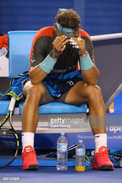 Rafael Nadal of Spain holds his face during a break in his men's final match against Stanislas Wawrinka of Switzerland during day 14 of the 2014...