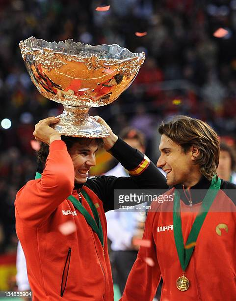 Rafael Nadal of Spain holds the Davis Cup trophy as he celebrates with his teammate David Ferrer during the third and last day of the final Davis Cup...