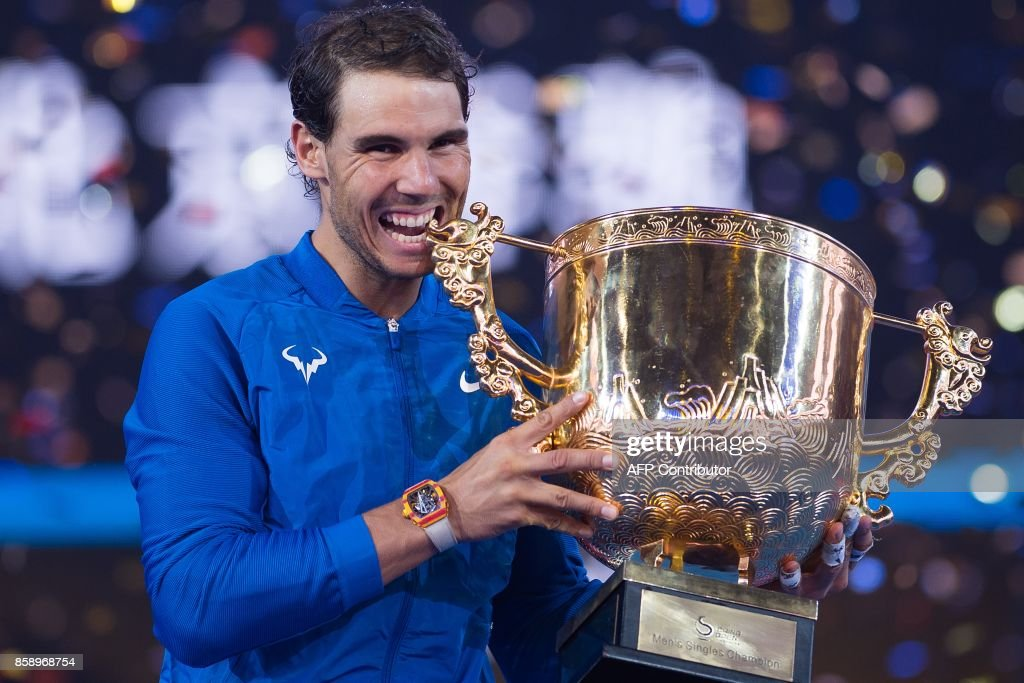 TOPSHOT - Rafael Nadal of Spain holds the trophy after winning the men's singles final match against Nick Kyrgios of Australia at the China Open tennis tournament in Beijing on October 8, 2017. /