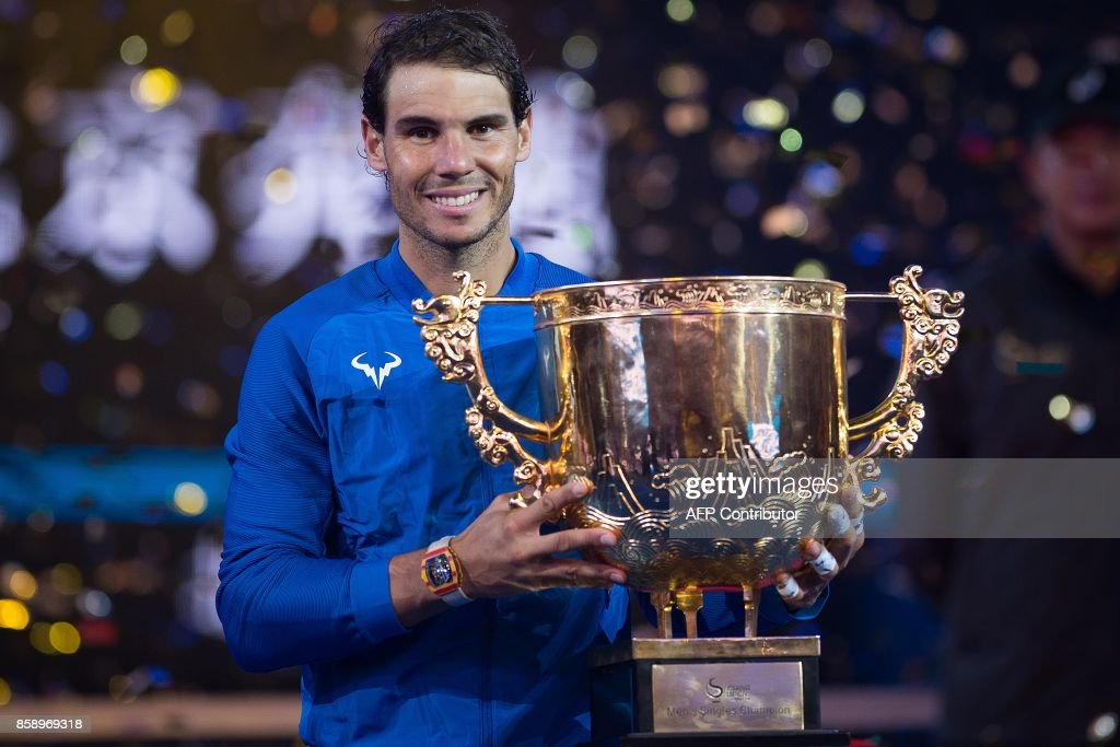 Rafael Nadal of Spain holds the trophy after winning the men's singles final match against Nick Kyrgios of Australia at the China Open tennis tournament in Beijing on October 8, 2017. /