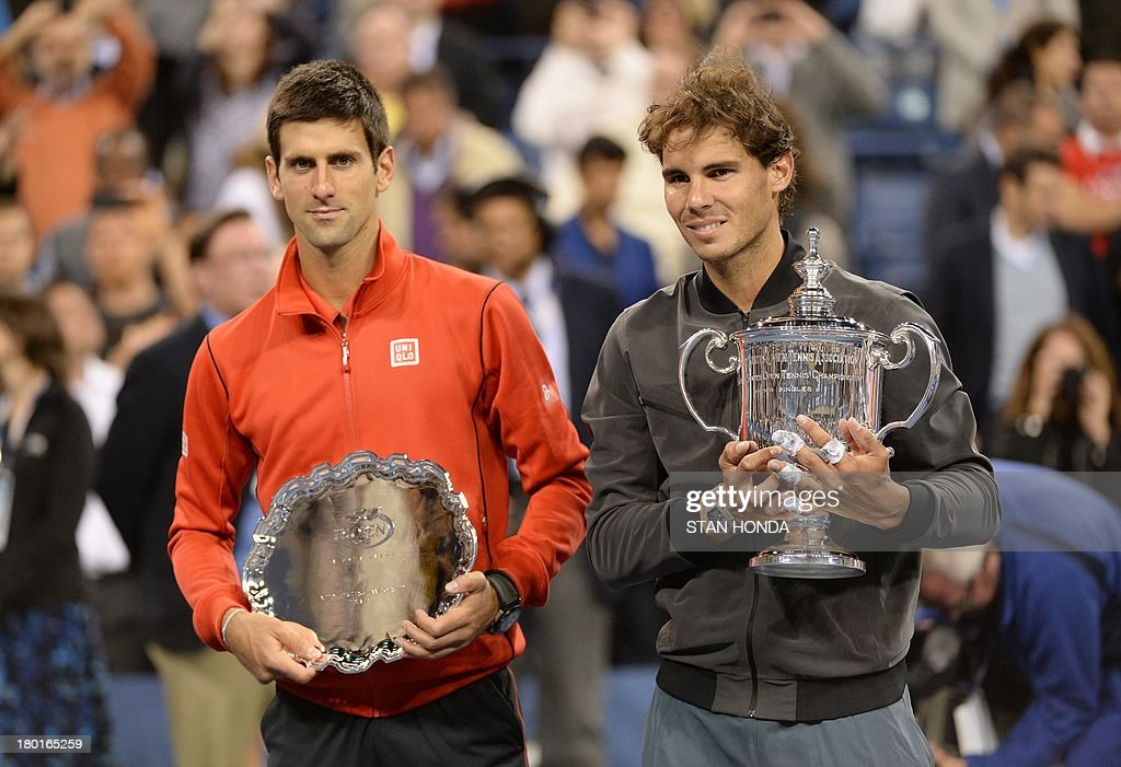 Rafael Nadal of Spain (R) holds the trophy as he celebrates his win over Novak Djokovic of Serbia (L) during their 2013 US Open men's singles final match at the USTA Billie Jean King National Tennis Center September 9, 2013 in New York. AFP PHOTO/Stan HONDA