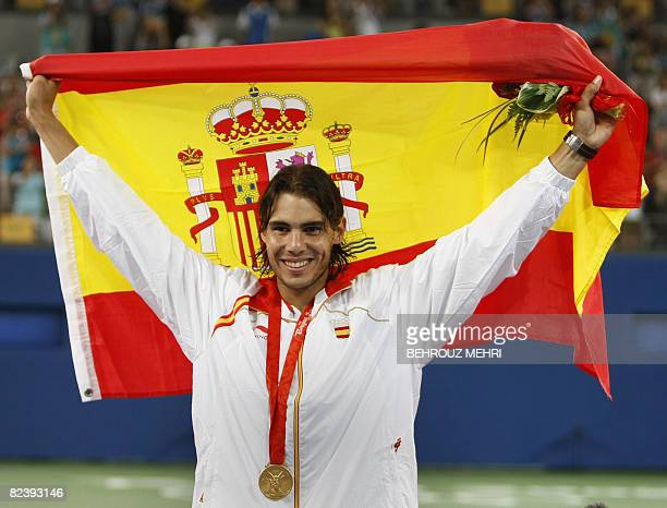 Rafael Nadal of Spain holds up the Spanish flag on the podium after receiving the gold medal for his victory over Fernando Gonzalez of Chile in their...