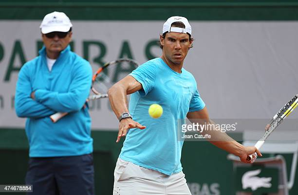 Rafael Nadal of Spain is practicing while his coach/uncle Toni Nadal looks on prior to the French Open 2015 at Roland Garros stadium on May 22 2015...