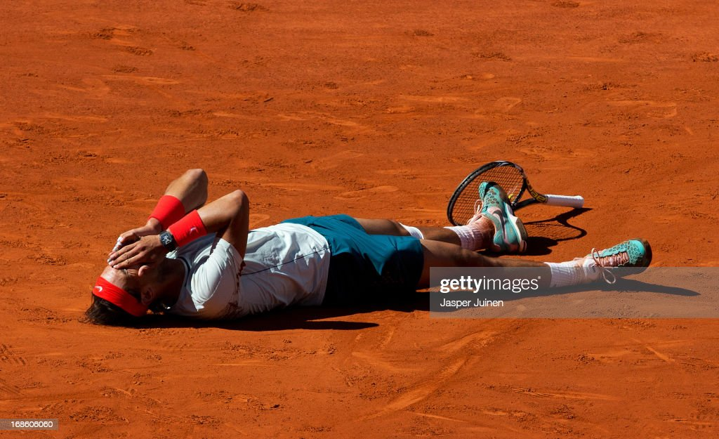 Rafael Nadal of Spain lays on his back covering his face celebrating matchpoint over Stanislas Wawrinka of Switzerland after winning the final match on day nine of the Mutua Madrid Open tennis tournament at the Caja Magica on May 12, 2013 in Madrid, Spain.