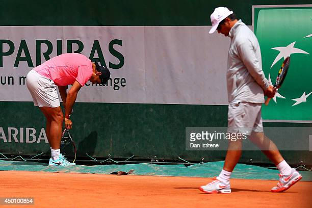 Rafael Nadal of Spain leans on his knee next to his coach and uncle Toni Nadal during a practice session on day twelve of the French Open at Roland...