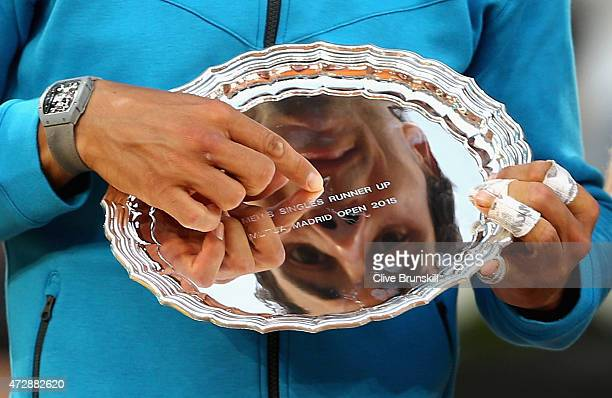 Rafael Nadal of Spain looks at his reflection in his runners up trophy after his straight sets defeat against Andy Murray of Great Britain in the...