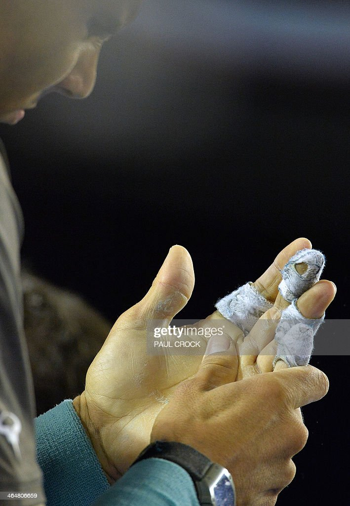 Rafael Nadal of Spain looks down at his bandaged hands during an injury time out while playing against Roger Federer of Switzerland during their men's singles semi-final match on day 12 of the 2014 Australian Open tennis tournament in Melbourne on January 24, 2014.