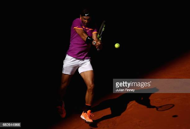 Rafael Nadal of Spain plays a backhand against Novak Djokovic of Serbia in the semi finals during day eight of the Mutua Madrid Open tennis at La...