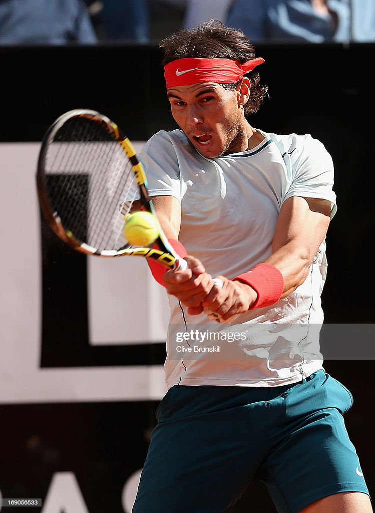 <a gi-track='captionPersonalityLinkClicked' href=/galleries/search?phrase=Rafael+Nadal&family=editorial&specificpeople=194996 ng-click='$event.stopPropagation()'>Rafael Nadal</a> of Spain plays a backhand against Roger Federer of Switzerland in their final match during day eight of the Internazionali BNL d'Italia 2013 at the Foro Italico Tennis Centre on May 19, 2013 in Rome, Italy.