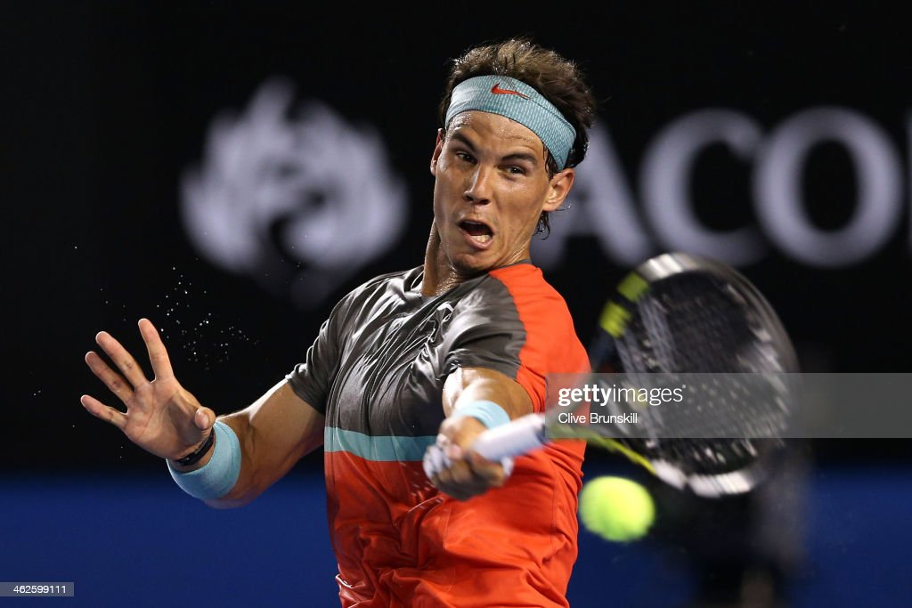 <a gi-track='captionPersonalityLinkClicked' href=/galleries/search?phrase=Rafael+Nadal&family=editorial&specificpeople=194996 ng-click='$event.stopPropagation()'>Rafael Nadal</a> of Spain plays a forehand in his first round match against Bernard Tomic of Australia during day two of the 2014 Australian Open at Melbourne Park on January 14, 2014 in Melbourne, Australia.