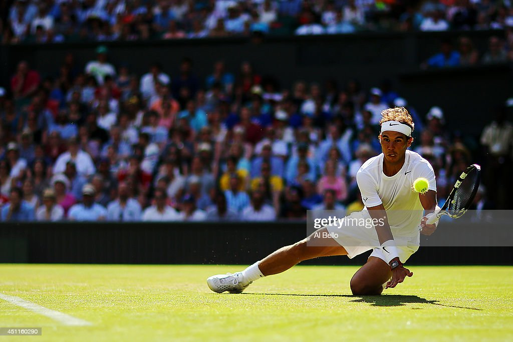Rafael Nadal of Spain plays the ball as he takes a tumble during his Gentlemen's Singles first round match against Martin Klizan of Slovakia on day two of the Wimbledon Lawn Tennis Championships at the All England Lawn Tennis and Croquet Club at Wimbledon on June 24, 2014 in London, England.