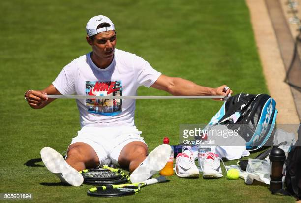 Rafael Nadal of Spain re grips his racket during a practice session ahead of the Wimbledon Lawn Tennis Championships at the All England Lawn Tennis...