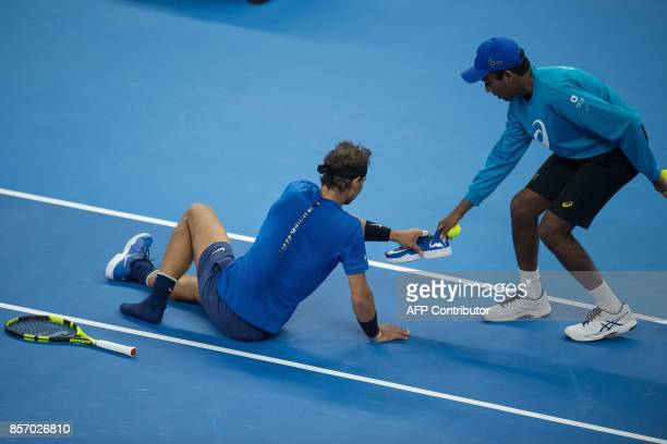 TOPSHOT Rafael Nadal of Spain receives his left shoe from a ball boy after Nadal slipped and fell during his men's singles match against Lucas...