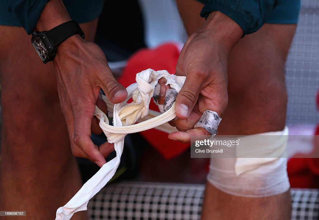 Rafael Nadal of Spain removes his knee bandages after his match against Roger Federer of Switzerland in their final match during day eight of the Internazionali BNL d'Italia 2013 at the Foro Italico Tennis Centre on May 19, 2013 in Rome, Italy.