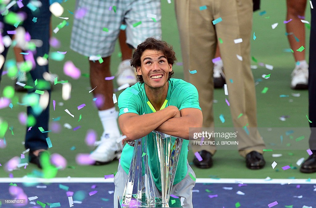 Rafael Nadal of Spain rests on the championship trophy as confetti is released after Nadal defeated Juan Martin Del Potro of Argentina in three-sets on March 17, 2013 in Indian Wells, California, in the men's tennis final at the BNP Paribas Open. AFP PHOTO/Frederic J. BROWN