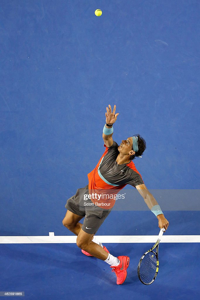 <a gi-track='captionPersonalityLinkClicked' href=/galleries/search?phrase=Rafael+Nadal&family=editorial&specificpeople=194996 ng-click='$event.stopPropagation()'>Rafael Nadal</a> of Spain serves in his first round match against Bernard Tomic of Australia during day two of the 2014 Australian Open at Melbourne Park on January 14, 2014 in Melbourne, Australia.