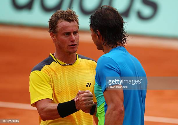 Rafael Nadal of Spain shakes hands at the net with Lleyton Hewitt of Australia after defeating him in their men's singles third round matchc on day...