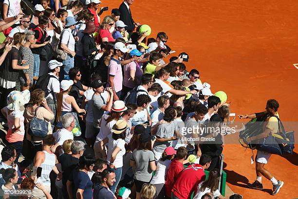 Rafael Nadal of Spain signs autographs after the doubles victory with Fernando Verdasco of Spain against Philipp Kohlschreiber of Germany and Viktor...