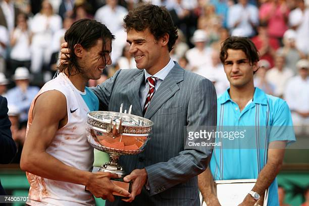 Rafael Nadal of Spain smiles as he holds the Philippe Chatrier Trophy after winning against Roger Federer of Switzerland with former winner Gustavo...
