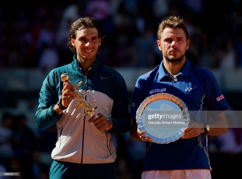 Rafael Nadal (L) of Spain stands with runner up Stanislas Wawrinka of Switzerland holding their trophies after Nadal won the final on day nine of the Mutua Madrid Open tennis tournament at the Caja Magica on May 12, 2013 in Madrid, Spain.