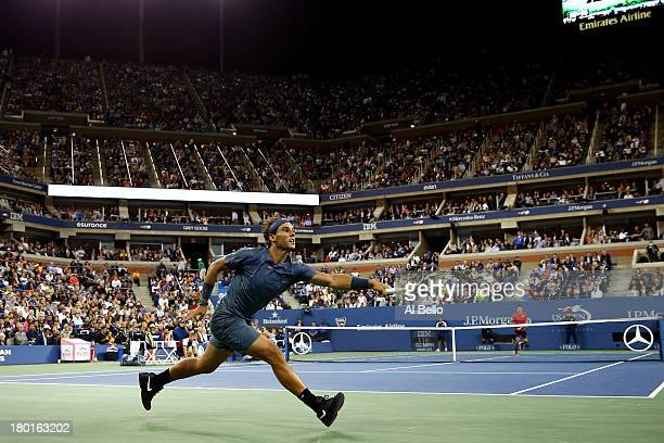 Rafael Nadal of Spain stretches to play a backhand during his men's singles final match against Novak Djokovic of Serbia on Day Fifteen of the 2013...