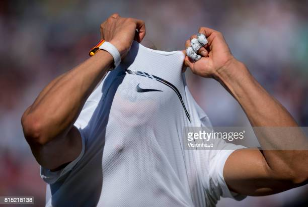 Rafael Nadal of Spain takes off his shirt after beating John Millman of Australia during the Wimbledon Lawn Tennis Championships at the All England...