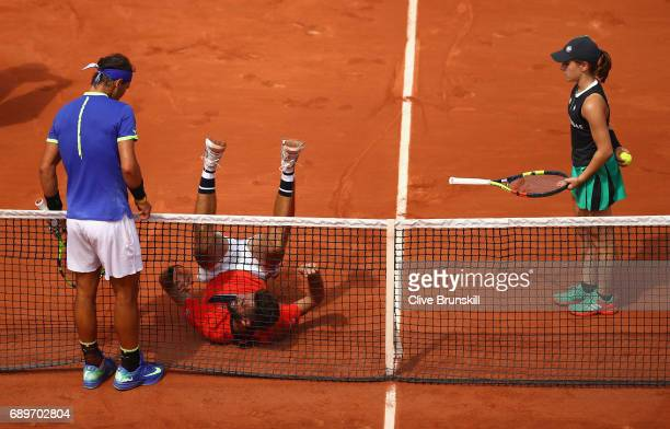 Rafael Nadal of Spain watches Benoit Paire of France fall into the net during their mens singles first round match on day two of the 2017 French Open...