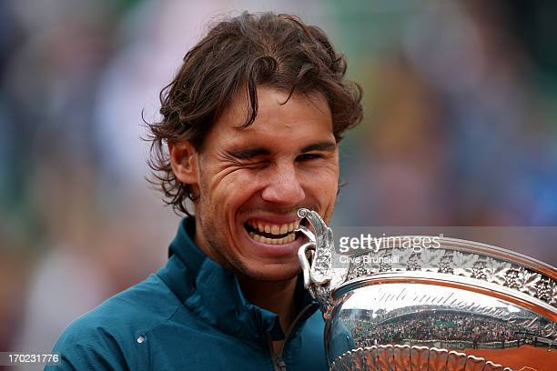 Rafael Nadal of Spain winks as hecelebrates and bites the Coupe des Mousquetaires trophy in the men's singles final against David Ferrer of Spain...