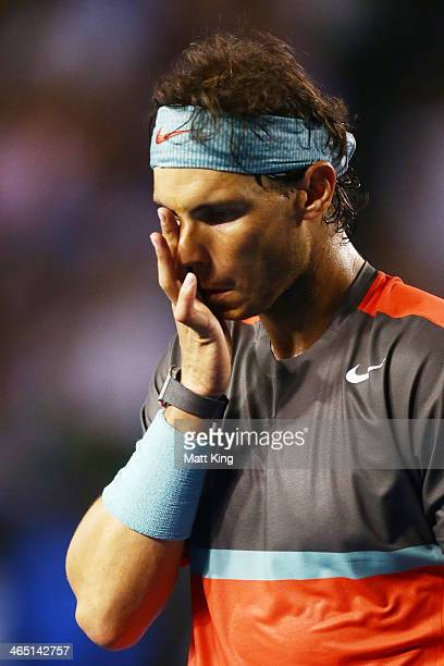 Rafael Nadal of Spain wipes his face in his men's final match against Stanislas Wawrinka of Switzerland during day 14 of the 2014 Australian Open at...
