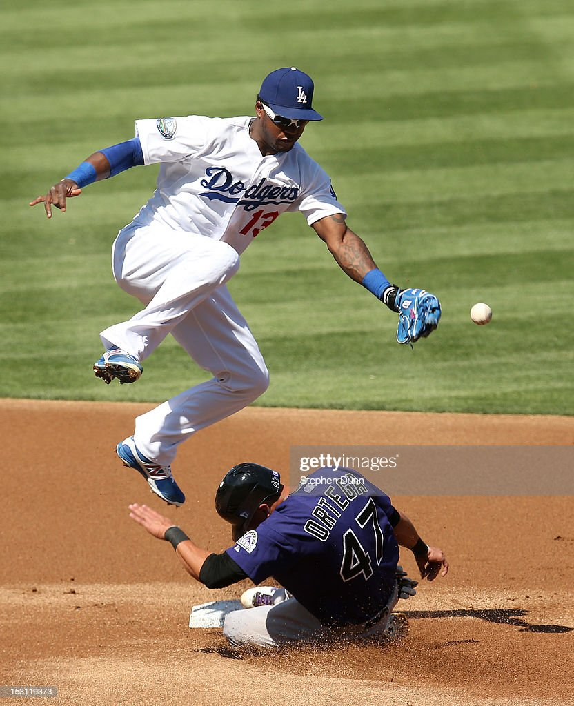 Rafael Ortega #47 of the Colorado Rockies slides into second with a stolen base as shortstop Hanley Ramirez #13 of the Los Angeles Dodgers can't handle th throw in the first inning on September 30, 2012 at Dodger Stadium in Los Angeles, California.