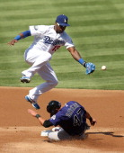 Rafael Ortega of the Colorado Rockies slides into second with a stolen base as shortstop Hanley Ramirez of the Los Angeles Dodgers can't handle th...