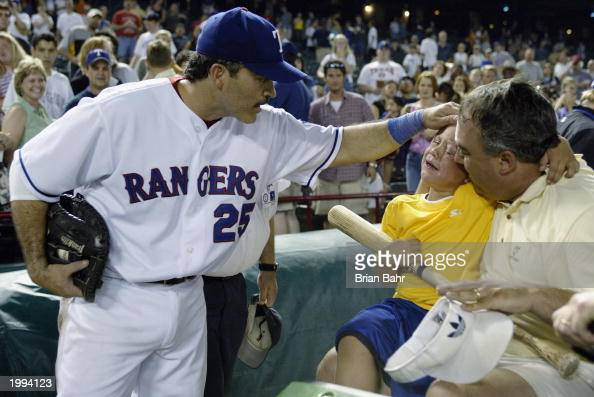 Rafael Palmeiro of the Texas Rangers gives a young fan a bat after he was nailed on the forehead by a hardhit foul ball during the bottom of the...