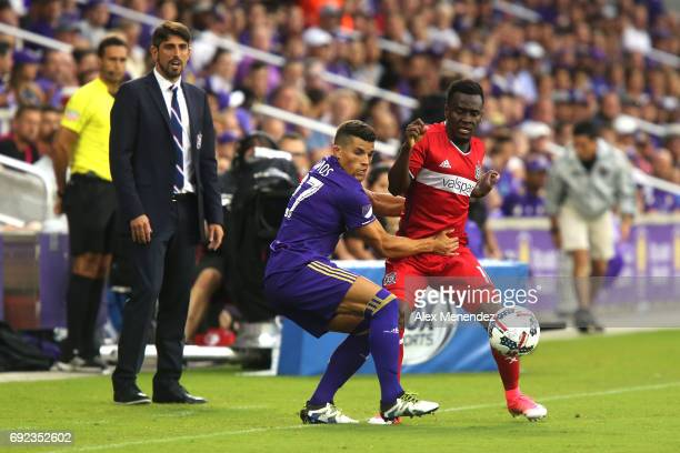 ORLANDO FL JUNE 4 Rafael Ramos of Orlando City SC grabs David Accam of Chicago Fire as Fire head coach Veljko Paunovic looks on during a MLS soccer...