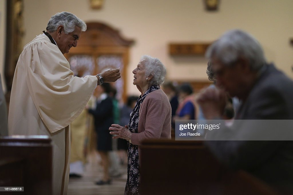 Rafael Ruiz (L) delivers communion to Maria Elena de la Vega during a service at the Church of the Little Flower on February 11, 2013 in Coral Gables, Florida. Parishioners today were dealing with the unexpected news that Pope Benedict XVI announced his retirement, now the wait begins to learn who his successor will be.