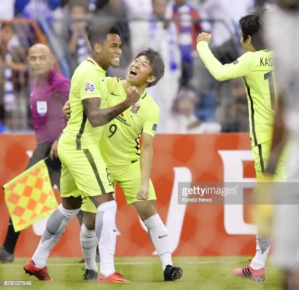 Rafael Silva a striker for Japan's Urawa Reds celebrates with teammates Yuki Muto and Yosuke Kashiwagi after scoring a goal in the first half of the...