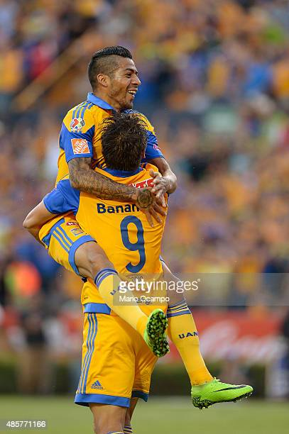 Rafael Sobis of Tigres celebrates with teammate his Javier Aquino after scoring his team's fourth goal during a 7th round match between Tigres UANL...