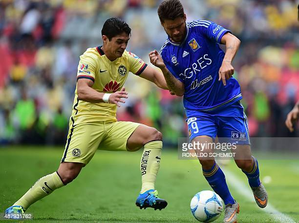 Rafael Sobis of Tigres vies for the ball with Javier Guemez of America during their Mexican Apertura tournament football match at the Azteca stadium...