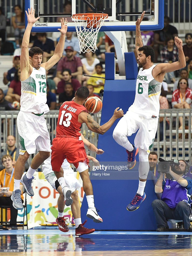 Rafael Souza #12 and Augusto Lima #6 of Brazil defend the basket as Jearrell De Jesus #13 of Puerto Rico drives during the 2015 Pan Am Games at the Ryerson Athletic Centre on July 21, 2015 in Toronto, Canada.