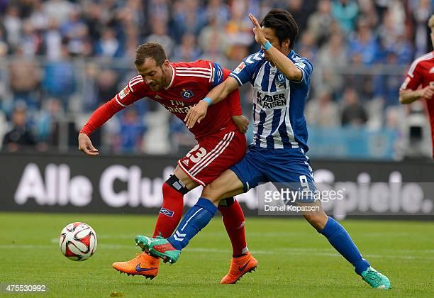 Rafael van der Vaart of Hamburg is challenged by Hiroki Yamada of Karlsruhe during the Bundesliga Playoff second leg match between Karlsruher SC and...