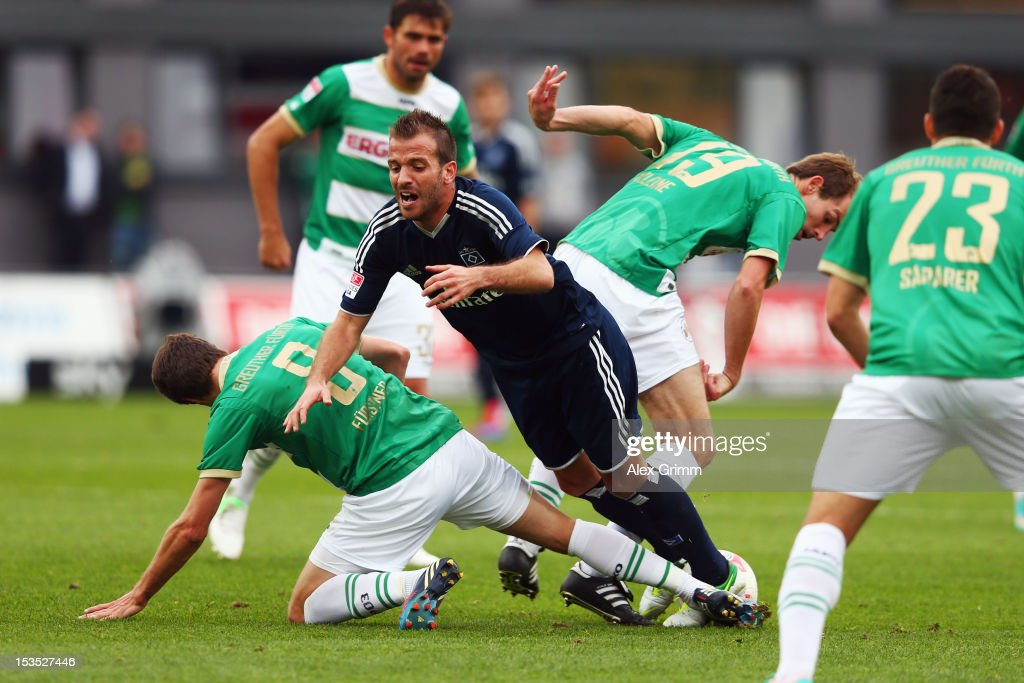 Rafael van der Vaart of Hamburg is challenged by Stefan Fuerstner, Thomas Kleine and Sercan Sararer (L-R) of Greuther Fuerth during the Bundesliga match between SpVgg Greuther Fuerth and Hamburger SV at Trolli-Arena on October 6, 2012 in Fuerth, Germany.