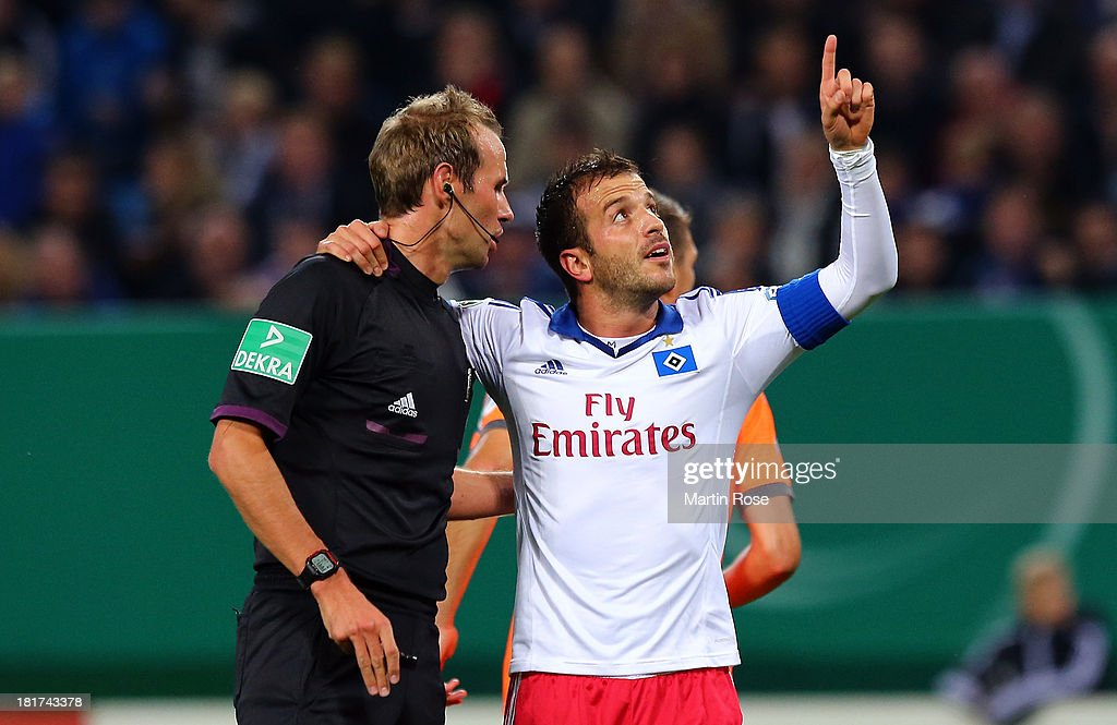 Rafael van der Vaart (R) of Hamburg jokes with referee Sascha Stegemann during the DFB Cup second round match between Hamburger SV and Greuther Fuerth at Imtech Arena on September 24, 2013 in Hamburg, Germany.