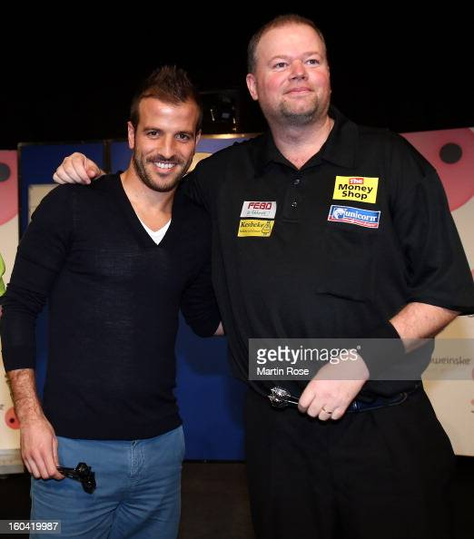 Rafael van der Vaart of Hamburg pose with Raymond van Barneveld of Netherlands during a dart show tournament at between team Netherlands and...