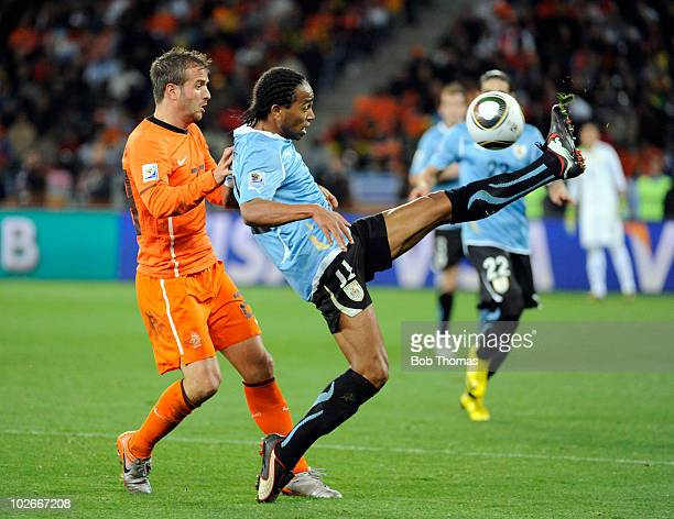 Rafael van der Vaart of the Netherlands watches Alvaro Pereira of Uruguay control the ball during the 2010 FIFA World Cup South Africa Semi Final...
