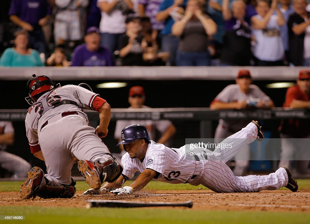 Rafael Ynoa of the Colorado Rockies attempts to stretch his two RBI triple into an inside the park home run and is tagged out by catcher Miguel...