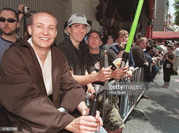 Rafal Karczmarczuk from Warsaw Poland and other Star Wars fans hold their homemade light sabres as they wait in line outside Mann's Chineese Theatre...