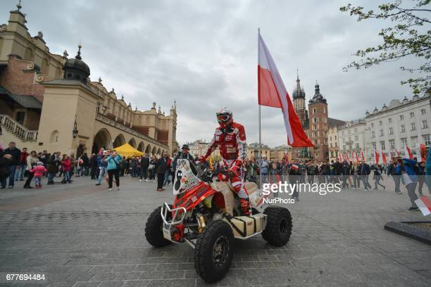 Rafal Sonik a Polish quad rally driver carries the Polish national flag on Krakow's Main Square during the 'White and Red relay' on Poland's Flag Day...