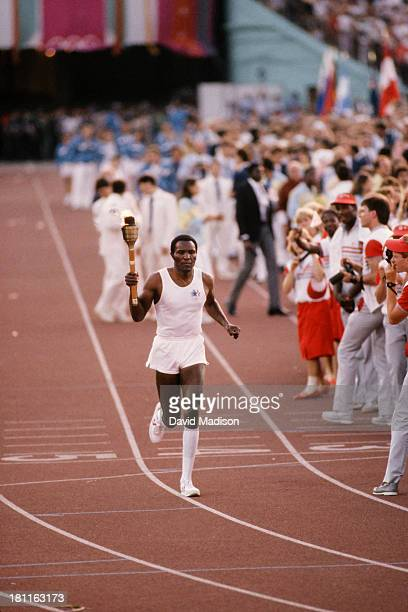 Rafer Johnson of the USA carries the Olympic Torch during the Opening Ceremony of the 1984 Summer Olympics at the Los Angeles Memorial Coliseum on...