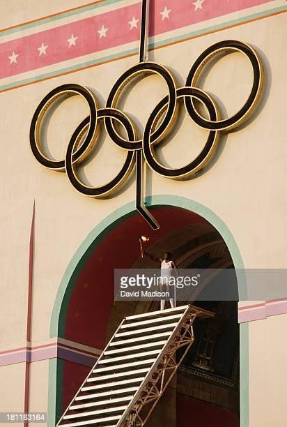 Rafer Johnson of the USA raises the Olympic Torch prior to lighting the Olympic Flame during the Opening Ceremony of the 1984 Summer Olympics at the...